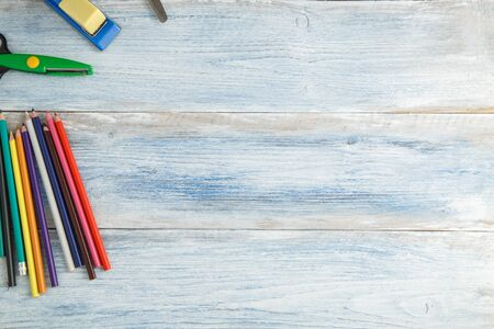 school children's concept. colored pencils,stapler and scissors on a blue and white scuffed vintage wooden background. the view from the top. Flat lay