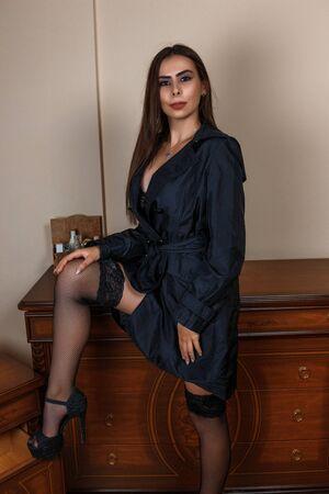 piękna kaukaska kobieta gospodyni domowa w czarnym płaszczu przeciwdeszczowym i w pięknej bieliźnie stoi obok toaletki w domu