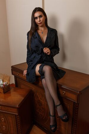 beautiful Caucasian woman housewife wife in black raincoat and beautiful lingerie sitting on the dressing table at home