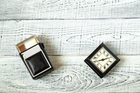 morning. vintage electric shaver and retro alarm clock on shabby white wooden background