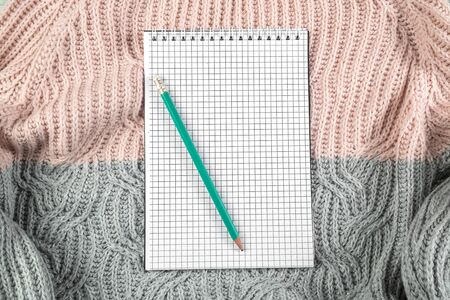 notebook on texture sweater with empty space for text. the view from the top. flat lay