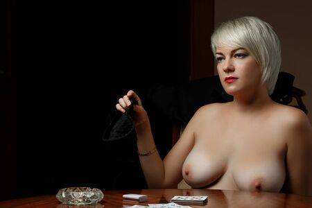 young Caucasian blonde woman sitting at a table and undressing after losing at cards