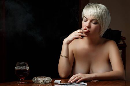 young Caucasian Nude blonde with bare Breasts sits at a table and smokes after losing at cards Stock Photo
