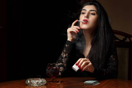 a beautiful brunette woman with scarlet lips in black clothes sits at a table, smokes and plays cards for undressing