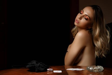 young caucasian woman sits at table with bare breasts after losing cards