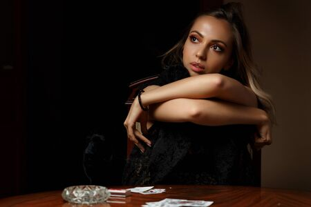 young Caucasian  woman undressing after losing at cards