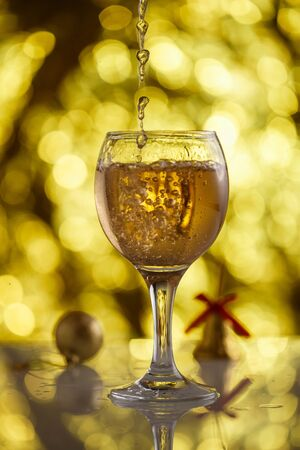 champagne glass on gold background with beautiful bokeh and Christmas toys Stockfoto