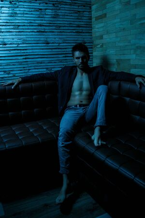 portrait of a young Caucasian guy in a black jacket on a naked body and gray jeans sitting in a stylish interior under the light of neon lights