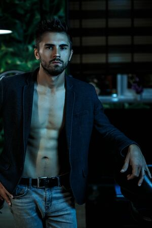 portrait of a young Caucasian guy in a black jacket on a naked body and gray jeans stands in a stylish interior in the light of neon lights
