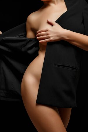 a woman in a black jacket on a naked body posing on a black background covering her Breasts Banco de Imagens