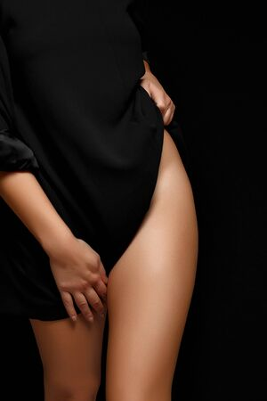 woman in black jacket on naked body posing on black background covering genitals Banco de Imagens