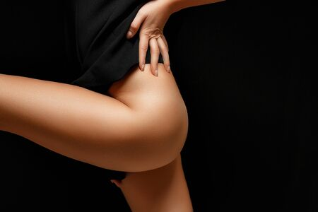 a woman in a black jacket on a naked body posing on a black background Baring her legs and hips Imagens