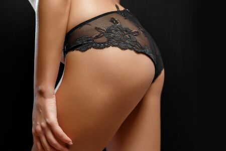 buttocks and body of young woman in black lingerie on black isolated background