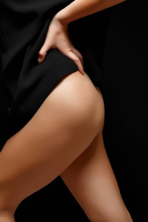 a woman in a black jacket on a naked body posing on a black background Baring her legs and hips Banco de Imagens