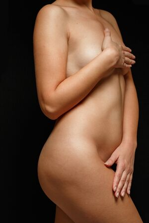 a fully Nude woman covering her body with postpartum and age related changes on a black background