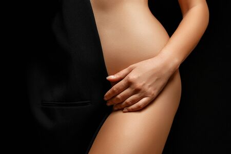 woman in black jacket on naked body posing on black background covering genitals Imagens