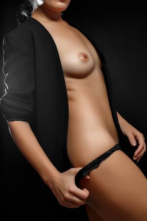naked Breasts and body of young woman in black jacket and black panties on black background