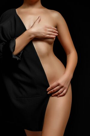a woman in a black jacket on a naked body posing on a black background covering her Breasts Imagens