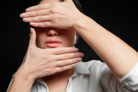 portrait of an Asian brunette woman in a white shirt covering her face with her hand on a black background