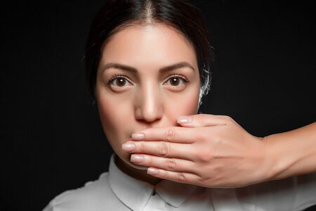 portrait of Asian brunette woman in white shirt with mouth covered by hand on black background Standard-Bild
