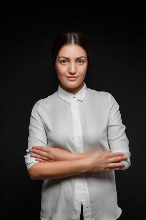 portrait of Asian brunette woman in white shirt and black leggings on black background Banco de Imagens