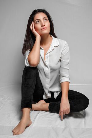a brunette woman in a white shirt and black leggings sits on a white background