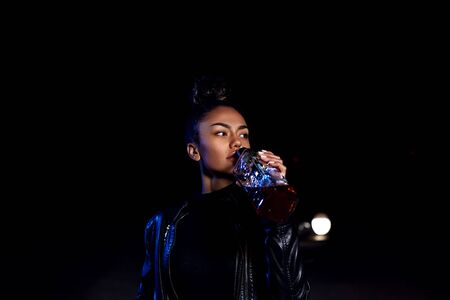 drunk young African American mulatto girl in a leather jacket and black clothes is on an abandoned sandy road drinking from a bottle of whiskey. at night in the light of car headlights and street lights
