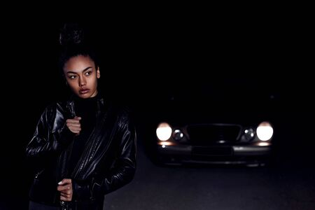 a young African American mulatto girl in a leather jacket and black clothes poses on an abandoned sand road. at night in the light of car headlights and lanterns