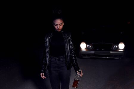 a young African-American mulatto girl in a leather jacket and black clothes is walking along an abandoned sandy road with a bottle of whiskey. at night in the light of car headlights and street lights Banco de Imagens