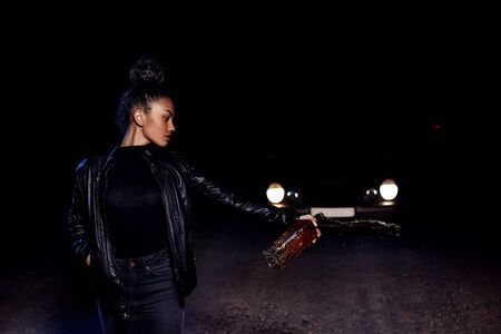 drunk young African American mulatto girl in a leather jacket and black clothes is on an abandoned sandy road empties a bottle of whiskey. at night in the light of car headlights and street lights Banco de Imagens