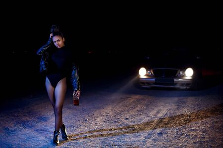 a young slender  girl in a leather jacket and bodysuit goes with a bottle of alcohol on an abandoned sandy road.at night in the light of car headlights and street lights