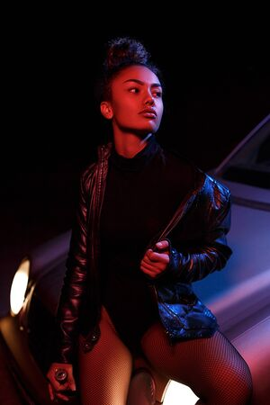 a young afro-american beautiful  girl in a leather jacket,in a bodysuit and with a bottle of alcoholic beverage poses on the hood of a car. stylish street light. night.