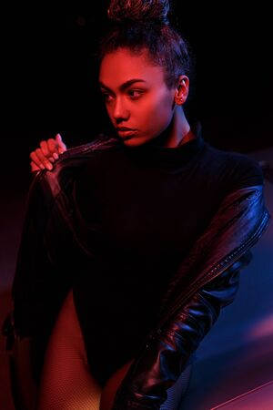 a young beautiful afro-american girl in a leather jacket, in a bodysuit posing on the hood of a car. stylish street light. night. Banco de Imagens