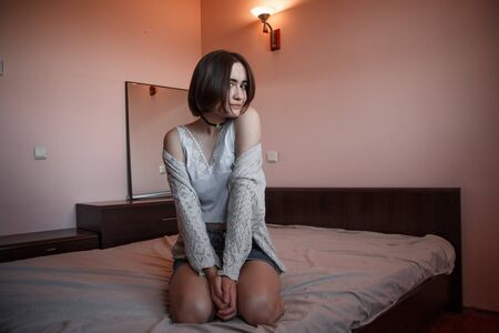 young girl with short hair in a sweater, denim skirt sitting alone on the bed in the bedroom in a good mood