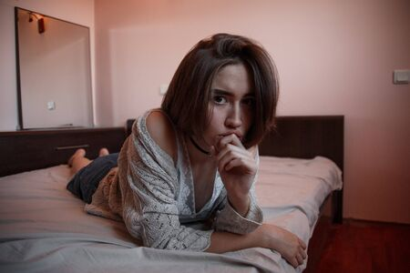 young girl with short hair in a sweater, denim skirt lying alone on the bed in the bedroom