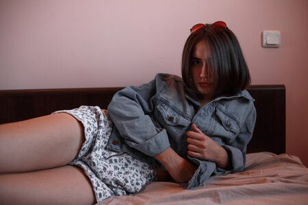 a young girl with short hair in a denim jacket and shorts lies alone on the bed