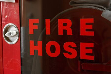 fire extinguisher box with the words fire hose . selective focus. shallow depth of focus