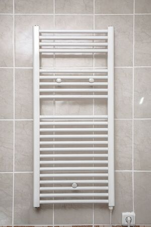 Stainless electric towel dryer for the bathroom. Drying is mounted on a wall with tiles. Towel dryer for drying towels in the bathroom