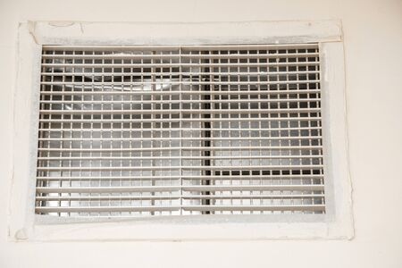 ventilation grille on the beige wall in the hall of an apartment building