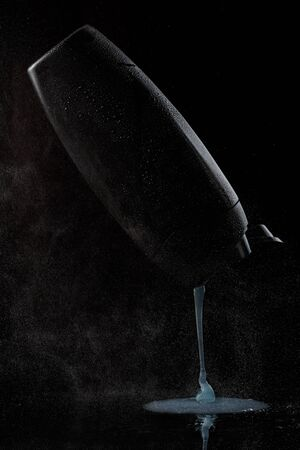 black sweaty plastic bottle for shampoo or shower gel from which the contents are poured on a black isolated background. as well as splashes of water or steam fall on the bottle