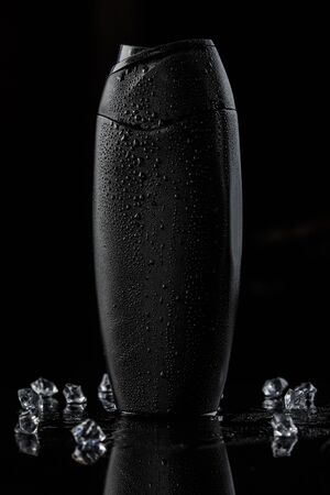 black sweaty plastic bottle for shampoo or shower gel on a black isolated background. there are also ice cubes in the background Stockfoto