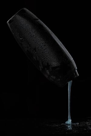 black sweaty plastic bottle for shampoo or shower gel from which the contents are poured on a black isolated background.