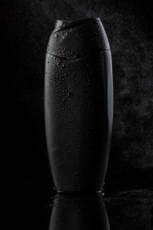 black sweaty plastic bottle for shampoo or shower gel on a black isolated background. as well as splashes of water or steam fall on the bottle