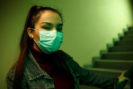 portrait of an Asian young woman in a protective disposable medical mask. stairwell of a hospital or building.
