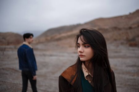 Dramatic portrait of a young brunette girl in cloudy weather. somewhere behind her, out of focus, her young lover boyfriend leaves her after break up . selective focus, small focus area. Banque d'images