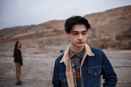 Dramatic portrait of a young brunette guy in cloudy weather. somewhere behind him, out of focus, his beloved leaves him . selective focus, small focus area