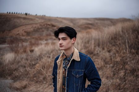 Dramatic portrait of a young brunette guy in cloudy weather against the background of mountains. selective focus, small focus area