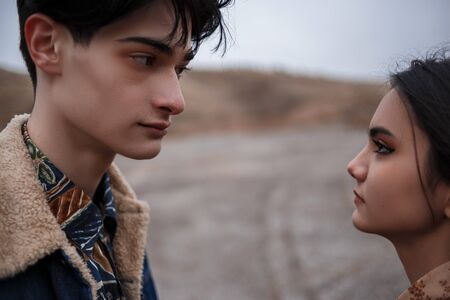 Dramatic portrait of a young brunette girl and a guy in cloudy weather.they look into each other's eyes . selective focus, small focus area