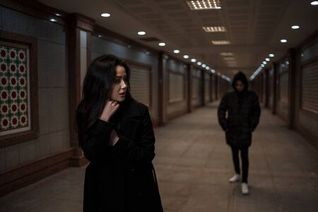 a young beautiful woman walks through an underground passage at night, followed by a man in dark clothes with a hood on his head