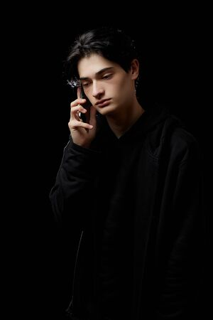 young guy in a black hoodie on a black background with a mobile phone in his hands